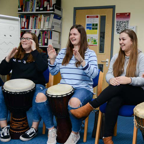 Students play the drums for a teamwork exercise